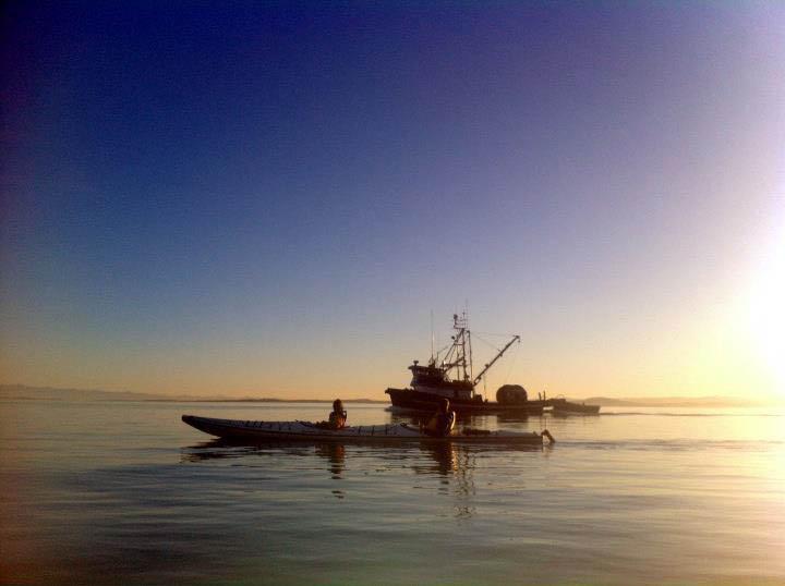 kayaking-along-side-fish-boat
