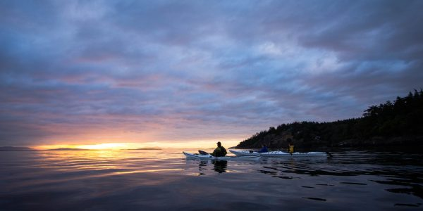 Beautiful sunset from kayak on San Juan Island with two kayakers