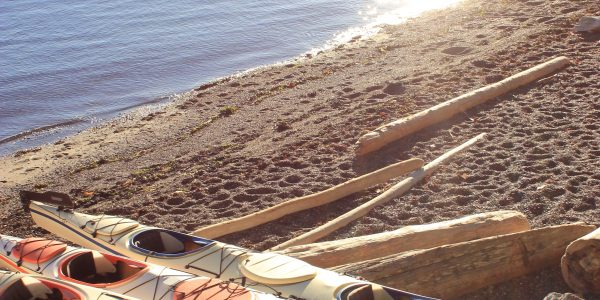 Kayaks on the beach with bright sun