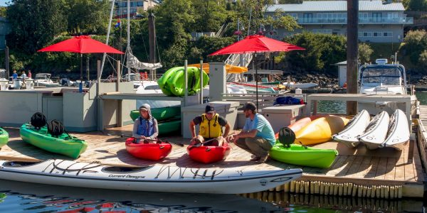 Guests getting paddling instruction on the docks with sit on top rental kayaks