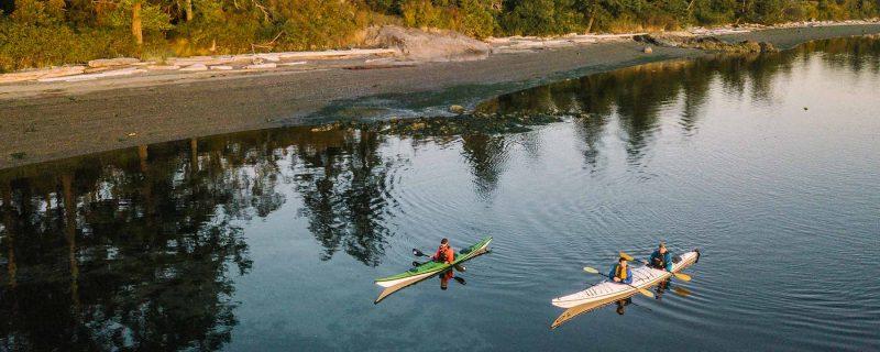 Kayakers paddling next to rocky beach